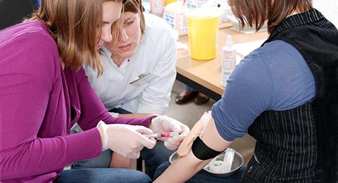 Studierende üben im Skills-Lab, wie man Blut abnimmt.
